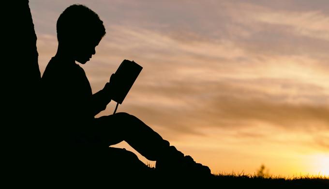 夕日をバッグに本を読んでいる少年の陰