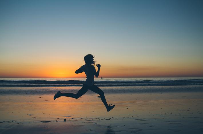 一人で海辺を走る女性