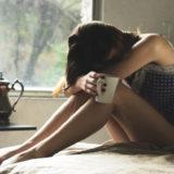 ベッドの上で体調不良に苦しむ女性の姿