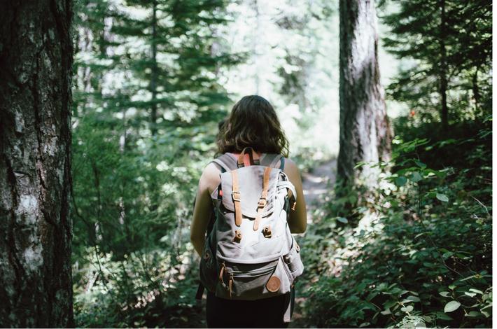 森林に囲まれた女性の後ろ姿