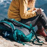 山登り中に休憩している女性の傍らに登山バックが置かれている