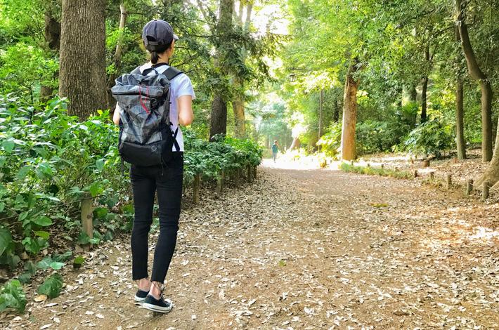 山と道miniを背負っている女性が公園を歩いている