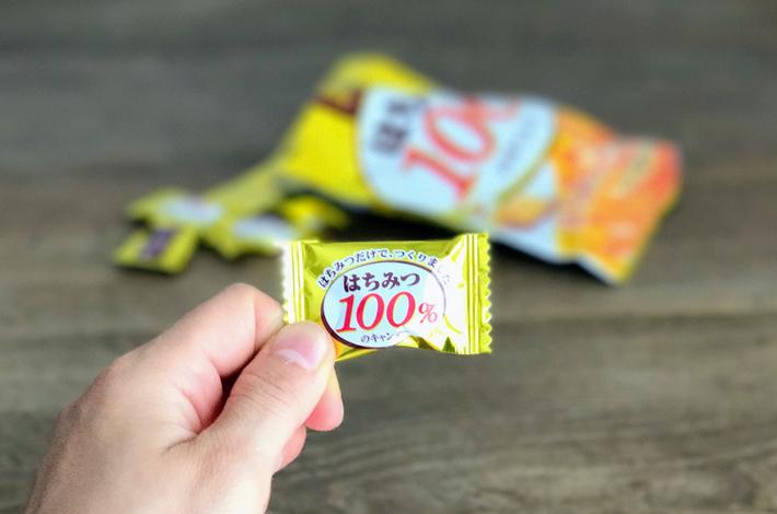 はちみつ100%キャンディーの1つを手に持っている