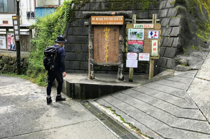御岳山へ徒歩の参道のゴールとした「御岳ビジターセンター」の前に男性が立っている