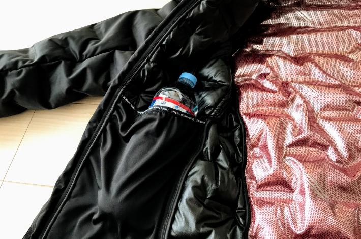 ワークマンプラスフィールドコア アルティメットフーデッドパーカーを男性が着て、内側のポケットにペットボトルを入れている