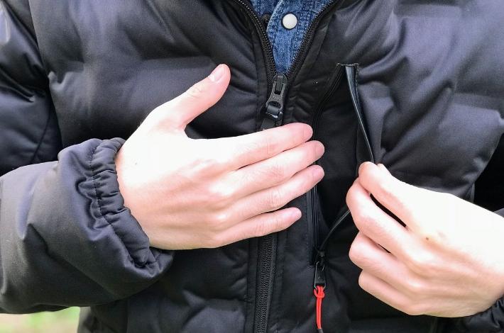 ワークマンプラスフィールドコア アルティメットフーデッドパーカーを男性が着て、左胸のポケットを開いている