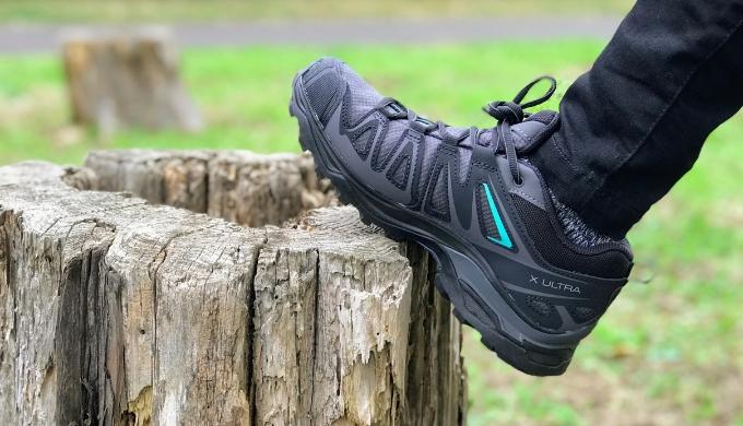 登山靴サロモン X ULTRA 3 PRIME GTXを女性が履いて切り株に靴をのせている状態