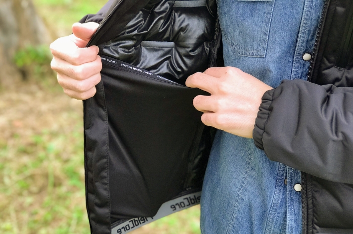 ワークマンプラスフィールドコア アルティメットフーデッドパーカーを男性が着て内側のポケットをのばしている