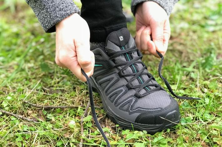 登山靴サロモン X ULTRA 3 PRIME GTXを女性が履いて紐を結んでいる