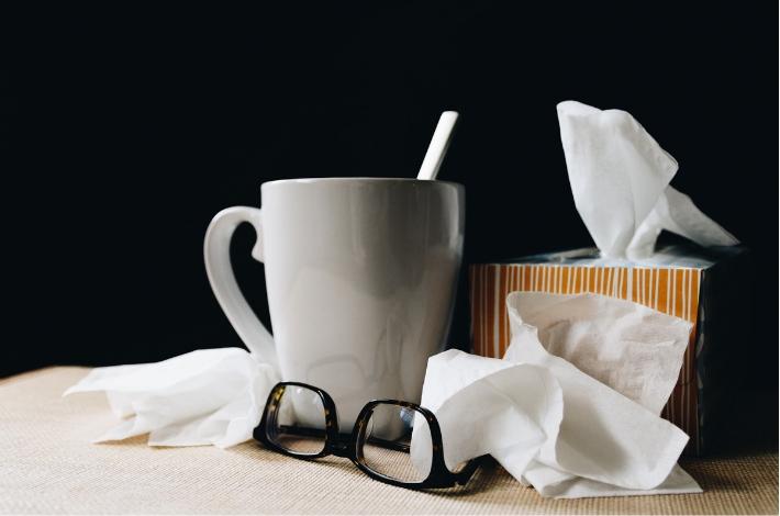 インフルエンザやノロウイルスにかかった時をイメージさせる、ティッシュやホットドリンクがテーブルに置かれている